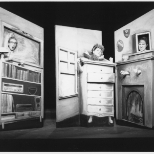 Black and White image showing a woman inside a chest of drawers
