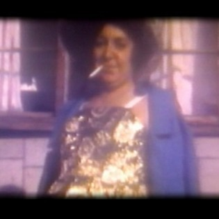 Still from Muffins for Granny, image of older woman in a dress with a cigarette in her mouth