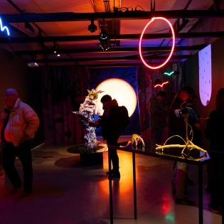 Dark room with people in foreground and works of art, neon light