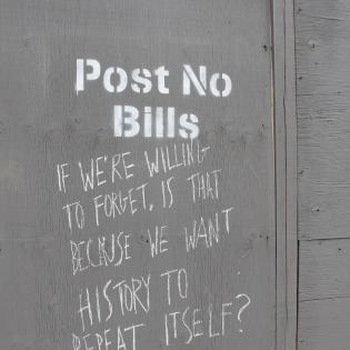 construction hoarding with 'post no bills' warning