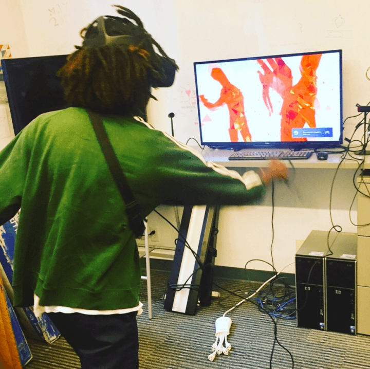 Photograph of a person using VR. Their right arm is extended forward as they move through the game world.