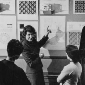 A woman points to a group of images on a wall in front of a group of people