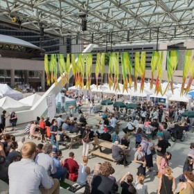 Image of crowd at Toronto Outdoor Art Fair with green banners in background