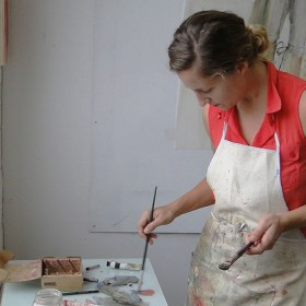 person in orange shirt painting in studio with paintbrush in paint