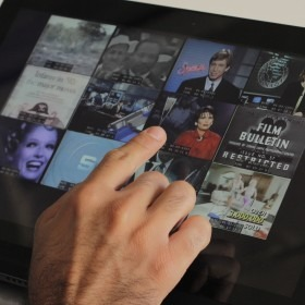 Photograph of a  person's hand, using a tablet to selecting images from the CBC News Holodeck