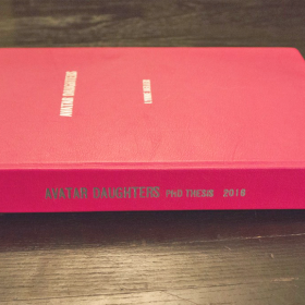 Photograph of a pink hardcover edition of Lynne Heller's PhD Thesis