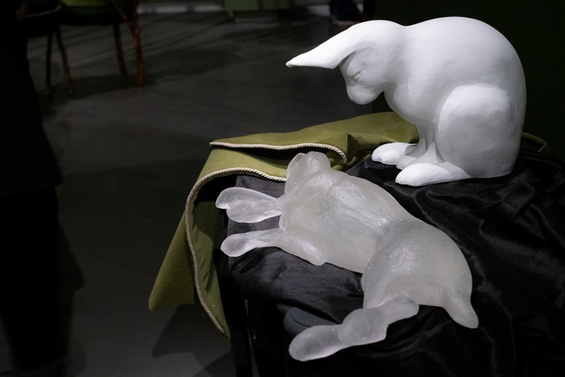 Sculpture of a rabbit looking down at a prone rabbit