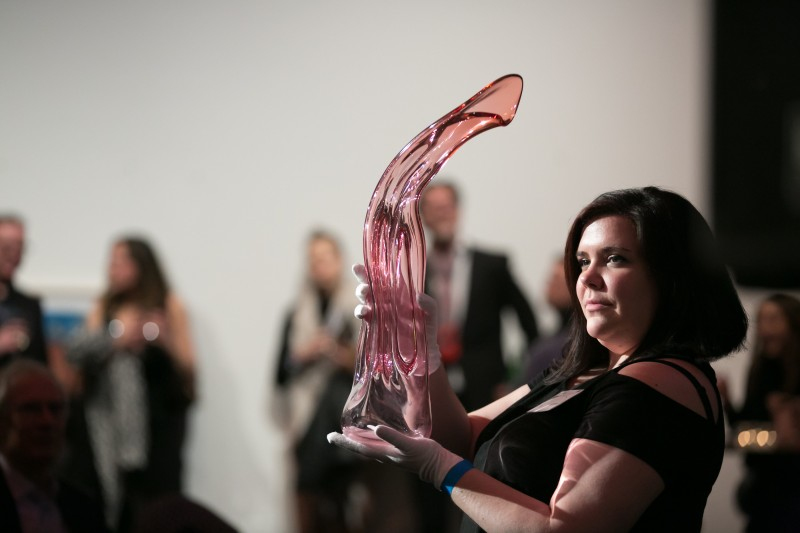 woman holding a pink blown glass sculpture