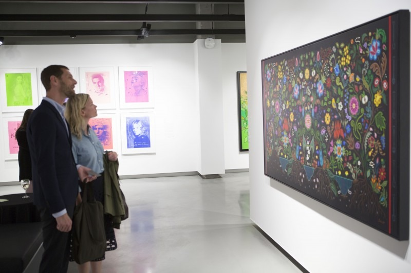two people looking at a large painting by Christi Belcourt