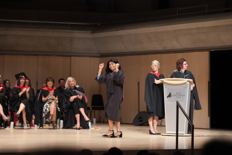 Young woman pumps fists as she crosses stage