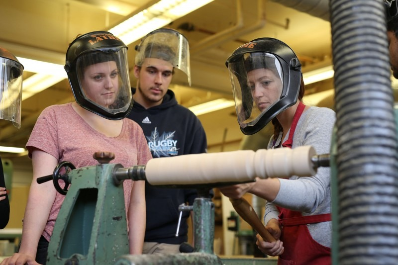 Three students working at a lathe