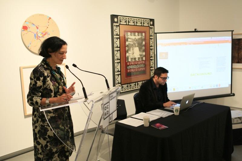 Dr. Sara Diamond at podium next to screen with presentation