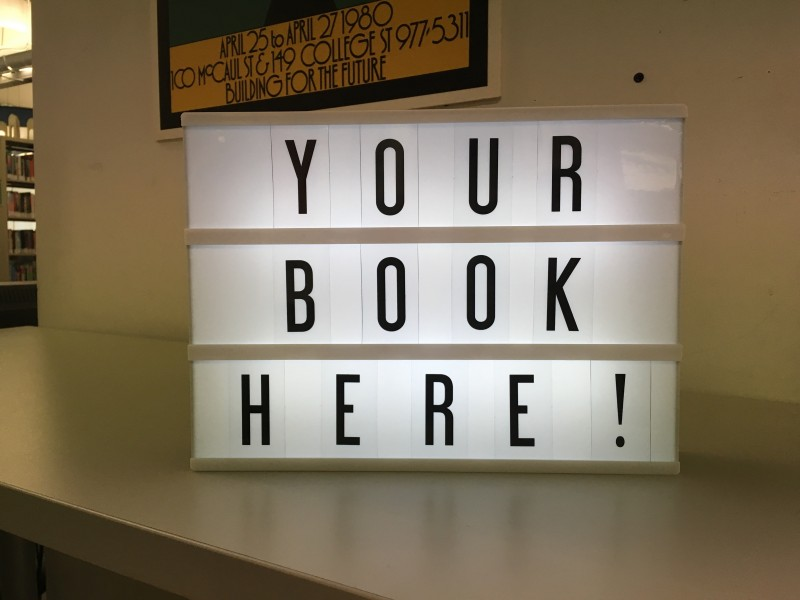 A photo of a Lightbox with marquee letters spelling: Your book here!