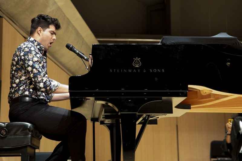 Jeremy Dutcher singing and playing a grand piano on stage at Roy Thomson Hall
