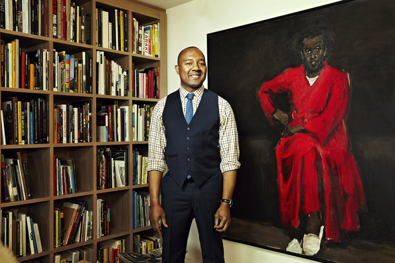 Image of Dr. Montague standing in front of a painting and bookshelf
