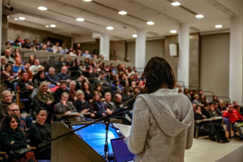 Woman at a podium facing an audience