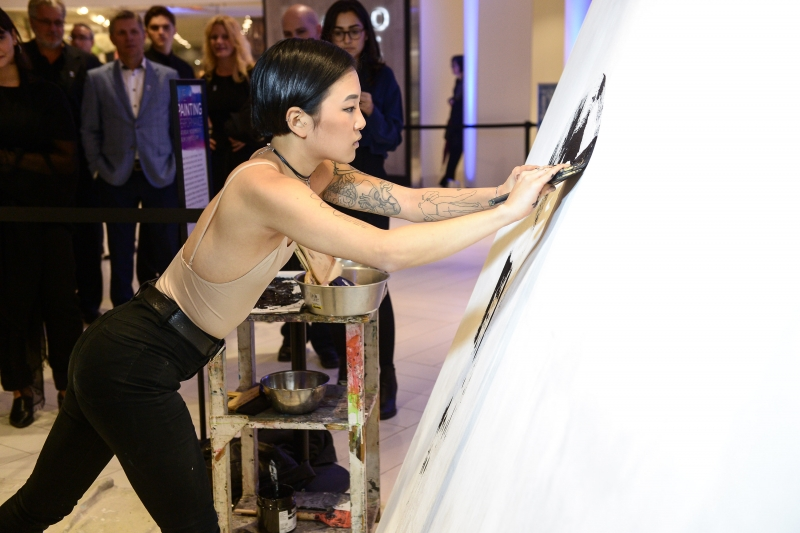 Woman painting on a large canvas