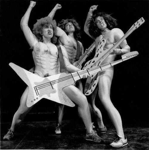 three people in costume posing with guitars