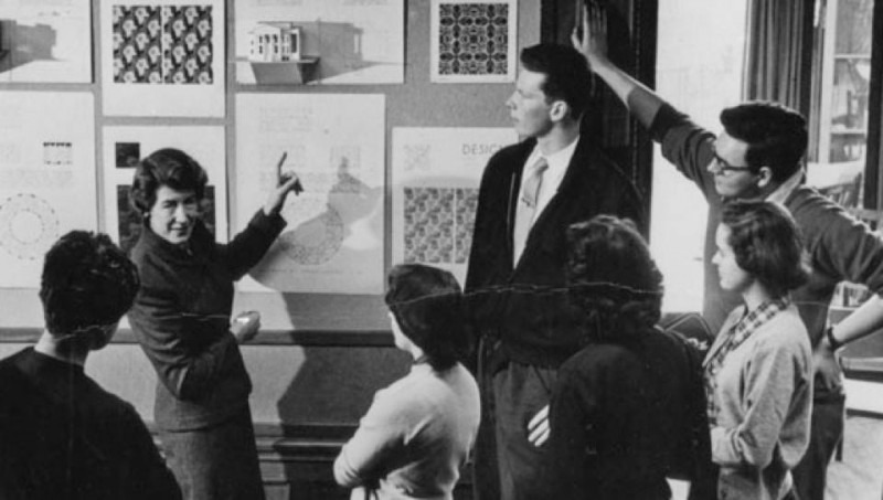 black and white photograph of a class looking at a wall of artwork