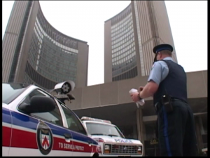 photo of police officer giving a ticket with city hall in the background