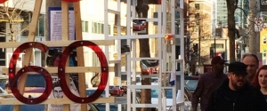 "Photograph of red plexiglass letters reading ""@60"" with people in the background."
