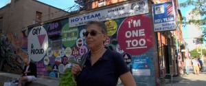 Still from Re:Orientations - Interview subject on a Toronto street, standing before a wall covered in LGBTQ-postive statements