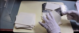 Image of gloved hands handling photograph.