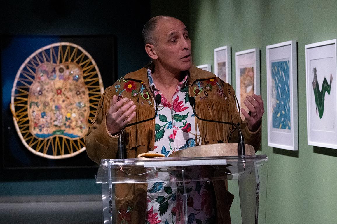 Archie Pechawis speaking at podium in gallery