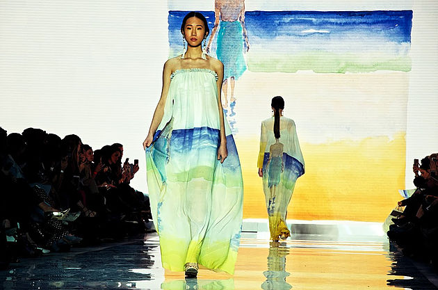 Model on runway wearing dress with watercolour image