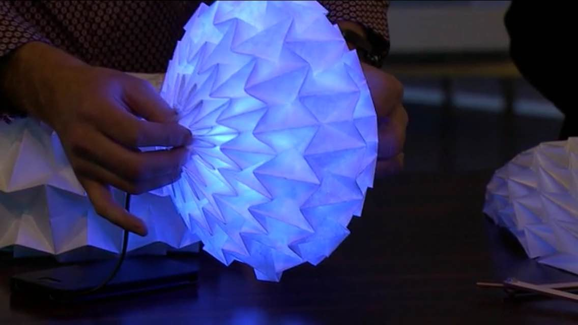 Ball made of pleated paper that expands and contracts, with lights inside