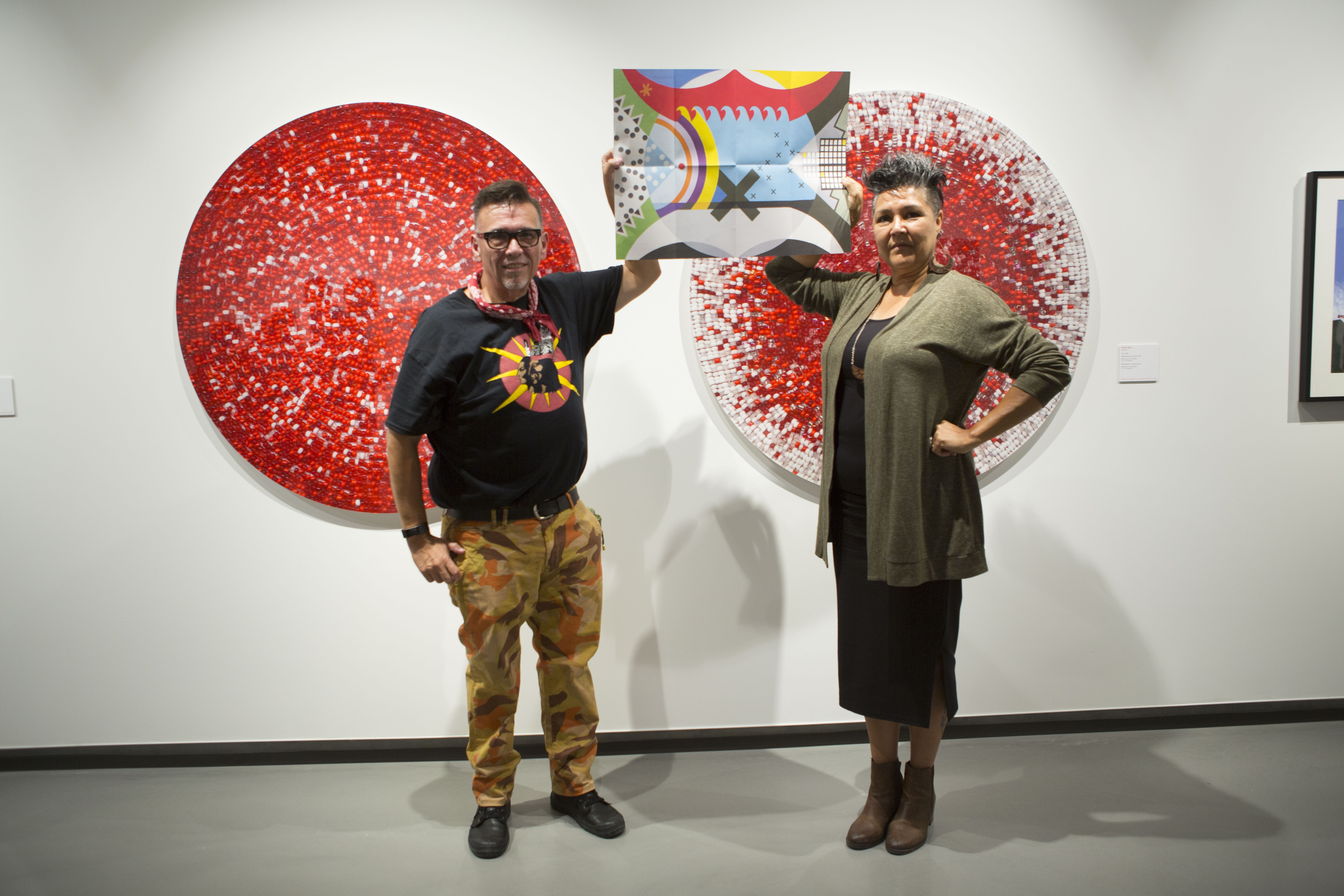 Ryan Rice with Janet Rogers, holding flag designed for exhibition