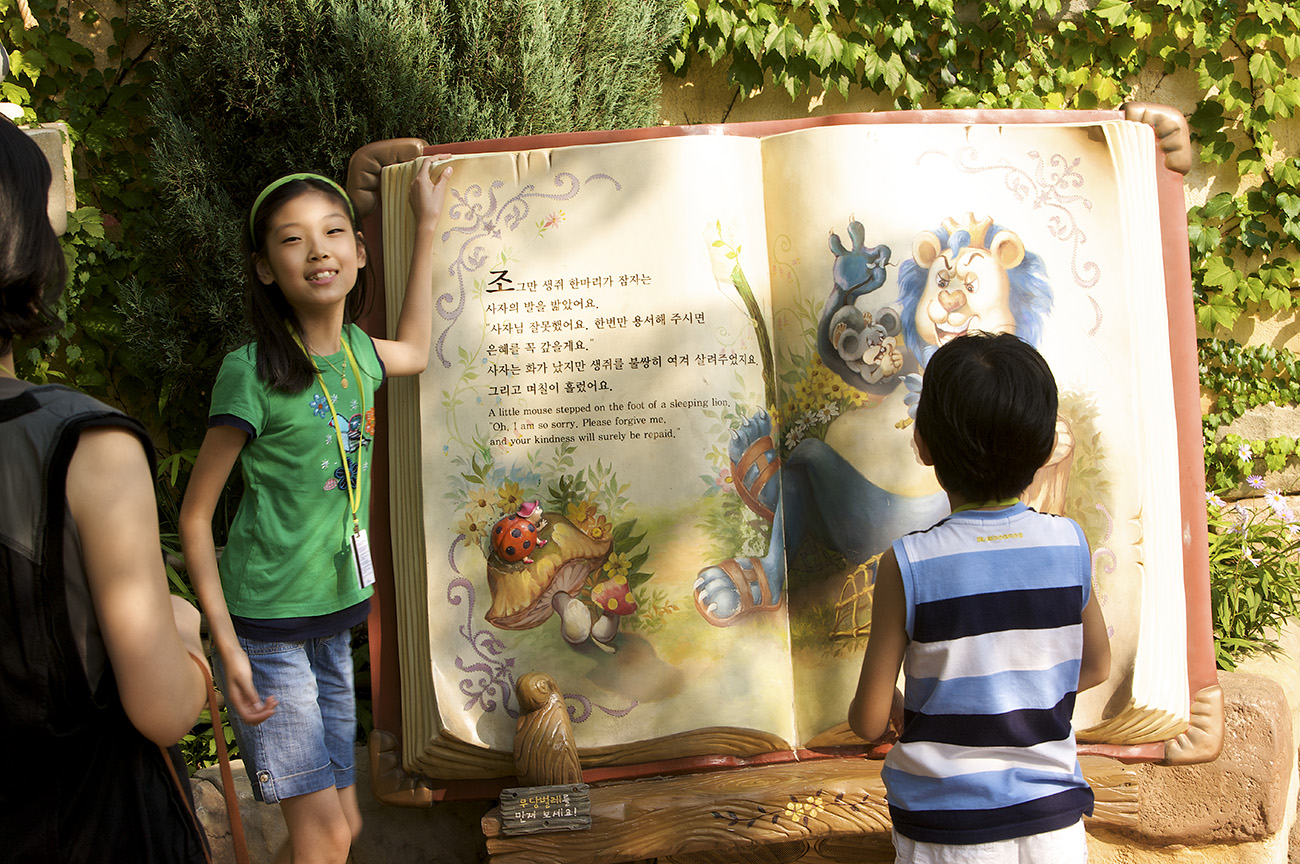 Young girl standing beside very large fairytale book, with young boy sitting and reading from the book