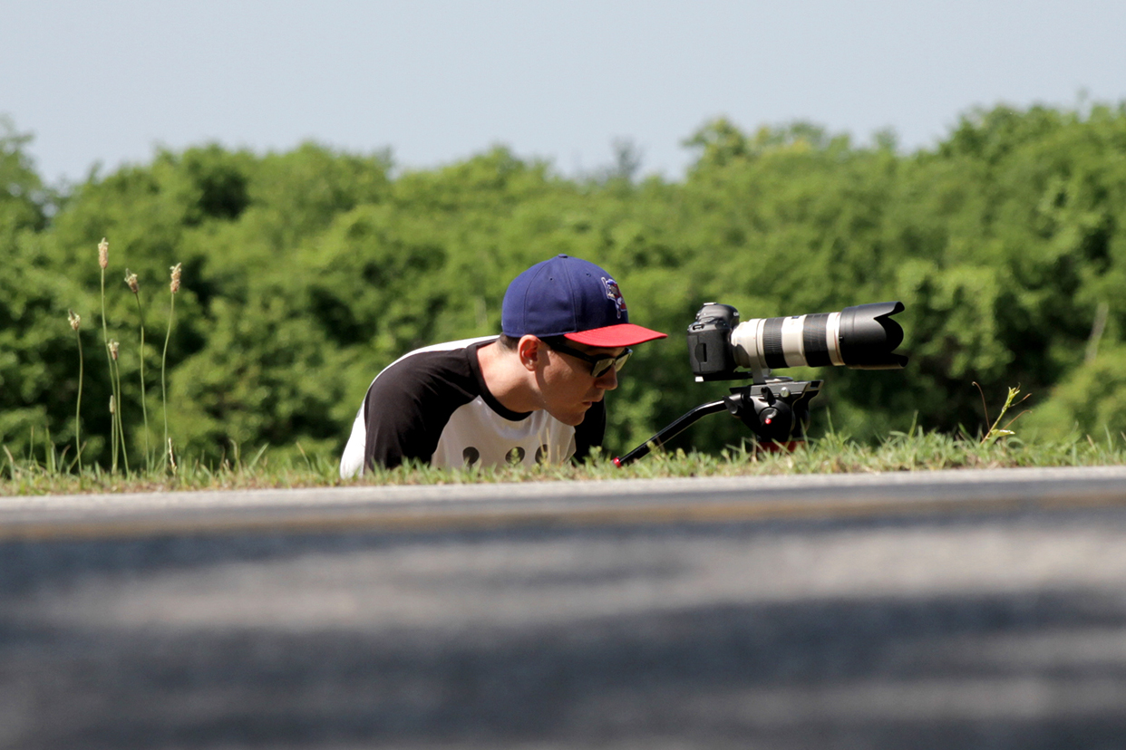 Image of Tom Briggs with camera, shooting bike race