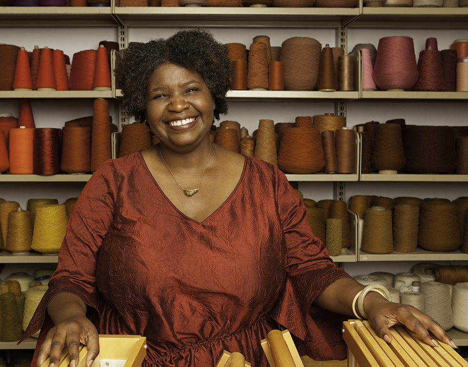 Dean Dori Tunstall standing in front of a wall of red, brown and pink thread spools