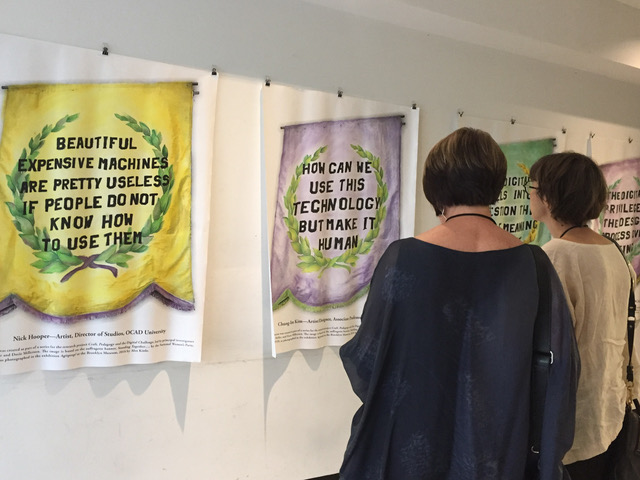 Photograph of viewers examining the hung posters