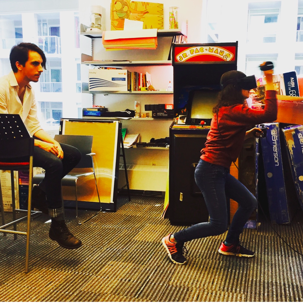 Photograph of two people: an immersant steps forward while interacting with VR and is observed by a second person