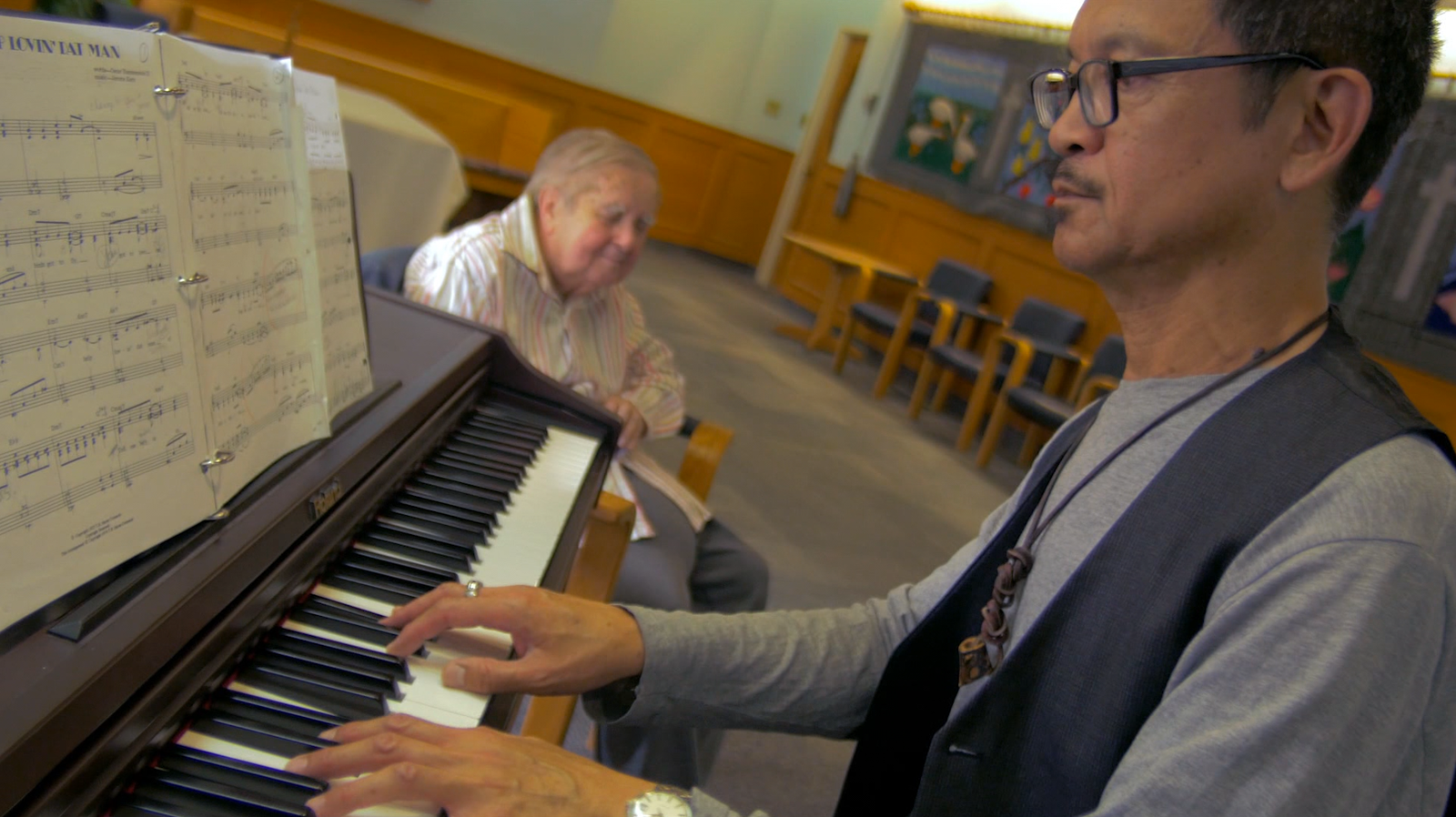 Film still: a photograph of a man playing the piano while an elderly man listens in the background.