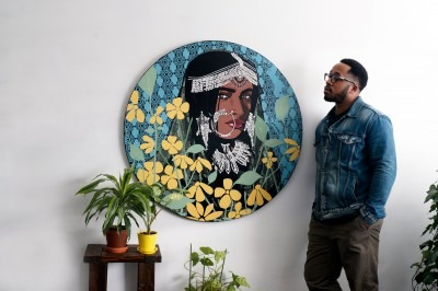 A photograph of Kestin Cornwall standing next to one of his paintings and several potted plants.