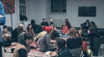 Photograph of participants in Post Colonial Hot-Ones event, seated on rugs and engaging in discussion
