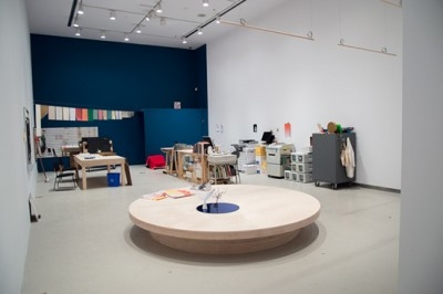 Image of a room with round tables and a blue wall