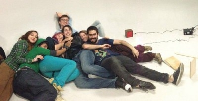 A group of young people laying with eachother