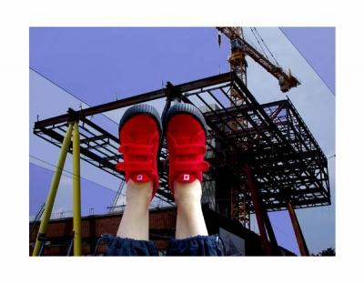 Photograph of the Sharp Centre under construction superimposed with a pair of upside-down feet wearing red shoes
