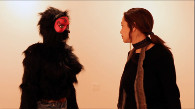 Image of two people, one masked, facing each other