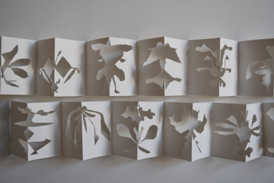 two rows of accordion folded paper with shapes cut out