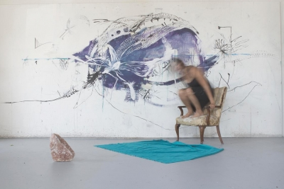 photo of a blurred woman on a chair with a painting behind her
