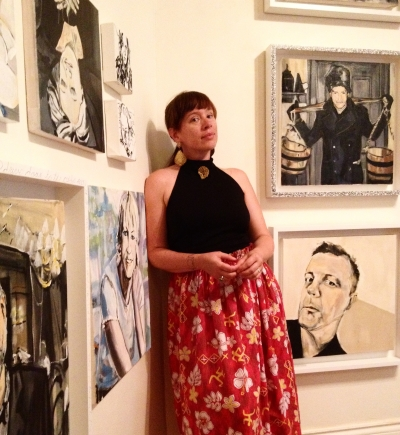 Photograph of the artist with multiple portraits hanging on the wall in the background