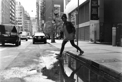 Black and White photo of woman stepping across a puddle
