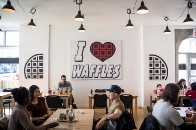 Image of students sitting inside of a waffle restaurant