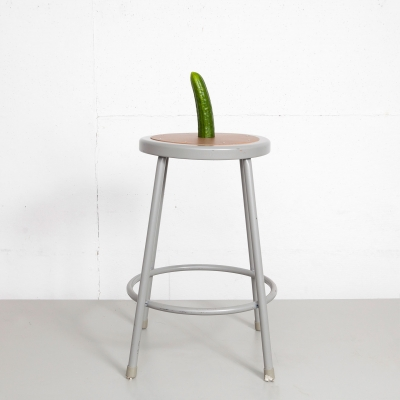 Photo of a cucumber wrapped in a condom, standing upright on a stool.