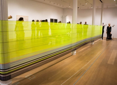 Photgraph of a woman standing at the far end of a gallery with a yellow band stretching the length of the room